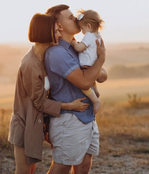 young-family-with-baby-daughter-on-the-sunset-in-field